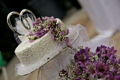 Weiße Hochzeitstorte mit purpurroten Blumen Lizenzfreie Stockfotografie