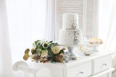 Weiße Hochzeitstorte mit silbernem Dekorations- und Hochzeitsblumenstrauß Stockbild