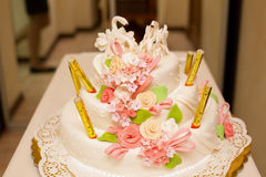 Weiße Hochzeitstorte und rosa Thetas mit Zahlen von Schwänen Stockfotografie