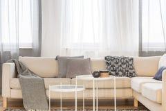 Weiße industrielle Couchtische im hellen Wohnzimmer Innen mit großer Eckcouch lizenzfreies stockbild
