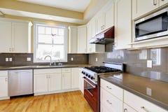 Weiße Küche mit Burgunder-Ofen und Graugegenoberteilen lizenzfreie stockbilder
