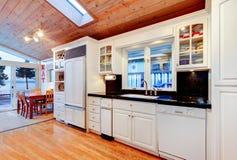 Weiße Küchenschränke mit schwarzen Gegenoberteilen im Luxushaus Stockbild