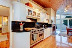 Weiße Küchenschränke mit schwarzen Gegenoberteilen im Luxushaus Stockfoto