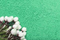 Weiße künstliche Rosen auf einem Frühling-grünen Hintergrund Lizenzfreies Stockfoto