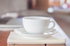 Weiße Kaffeetasse auf Arbeitsplatz Stockbild
