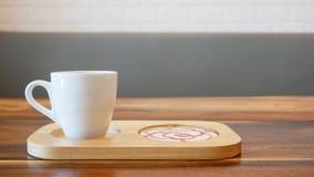 Weiße Kaffeetasse auf hölzerner Platte lizenzfreie stockfotografie