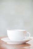 Weiße Kaffeetasse auf hölzerner Tabelle Stockfotografie