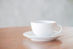 Weiße Kaffeetasse auf hölzerner Tabelle Lizenzfreie Stockfotografie