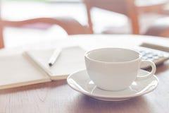 Weiße Kaffeetasse auf hölzerner Tabelle Stockfotos