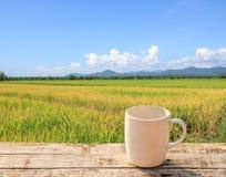 Weiße Kaffeetasse auf Holztisch mit grünem backgroun des ungeschälten Reises Lizenzfreies Stockfoto
