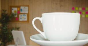 Weiße Kaffeetasse auf Untertasse gegen undeutliches Büro mit dunkler Überlagerung Lizenzfreie Stockbilder