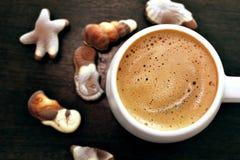 Weiße Kaffeetasse Cappuccino und belgische Schokolade des Feinschmeckers auf einem Holztisch Stockfotos