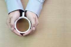 weiße Kaffeetasse in der Hand eines Geschäftsmannes auf einem braunen hölzernen floo lizenzfreie stockbilder