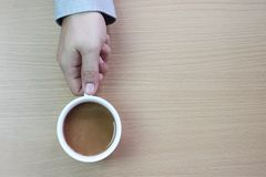 weiße Kaffeetasse in der Hand eines Geschäftsmannes auf einem braunen hölzernen floo lizenzfreie stockfotografie