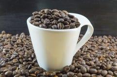 Weiße Kaffeetasse füllte mit den Kaffeebohnen, die auf gebratenes coff gesetzt wurden Stockbild