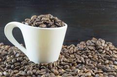 Weiße Kaffeetasse füllte mit den Kaffeebohnen, die auf gebratenes coff gesetzt wurden Lizenzfreies Stockfoto