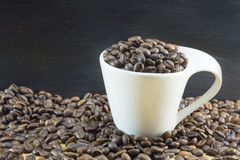Weiße Kaffeetasse füllte mit den Kaffeebohnen, die auf gebratenes coff gesetzt wurden Lizenzfreies Stockbild