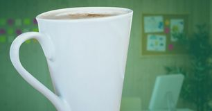 Weiße Kaffeetasse gegen undeutliches Büro mit grüner Überlagerung Lizenzfreies Stockbild