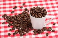 Weiße Kaffeetasse mit braunen Kaffeebohnen Stockbild