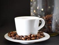 Weiße Kaffeetasse mit Kaffeebohnen stockbild
