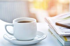 weiße Kaffeetasse am Morgen mit Zeitung und Buch auf Tabelle Stockbilder