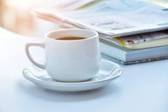 weiße Kaffeetasse am Morgen mit Zeitung und Buch auf Tabelle Stockfotos
