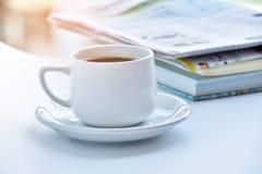 weiße Kaffeetasse am Morgen mit Zeitung und Buch auf Tabelle Lizenzfreie Stockfotos