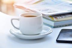 weiße Kaffeetasse am Morgen mit Zeitung und Buch auf Tabelle Lizenzfreie Stockbilder