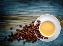 Weiße Kaffeetasse und Bohnen auf altem hölzernem Hintergrund Stockfoto