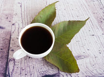 Weiße Kaffeetasse und Herbstlaub Lizenzfreie Stockfotografie