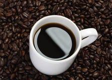 Weiße Kaffeetasse und Kaffeebohnen Stockbilder
