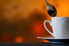 Weiße Kaffeetasse und Löffel auf einem undeutlichen Hintergrund für die Werbung oder abstrakten Hintergrund Lizenzfreie Stockbilder