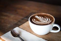 Weiße Kaffeetassekunst mit Löffel, Gewebe, hackendes Brett auf Holztisch in der Kaffeestube Abbildung der roten Lilie Stockfoto