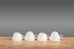 Weiße Kaffeetassen auf dem Holztisch Lizenzfreie Stockfotos