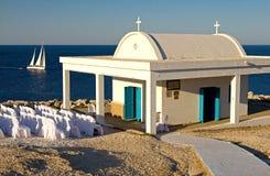 Weiße Kapelle mit Segelboot, Zypern Lizenzfreies Stockbild