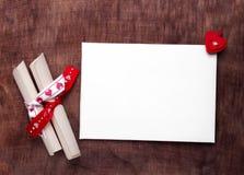 Weiße Karte mit einem roten Herzen auf hölzernem Hintergrund Stockfotografie