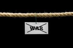 Weiße Karte mit Text Krieg kreuzte durch das Hängen von einem Seil Lizenzfreies Stockbild