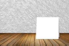 Weiße Karte setzte an hölzernen Schreibtisch oder Bretterboden auf unscharfen abstrakten weißen Wandbeschaffenheitshintergrund Ge Stockfotografie