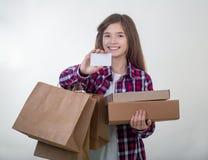 Weiße Karte und Einkaufstaschen des glücklichen Holdingrabattes des jungen Mädchens in ihren Händen Mädchen mit Kreditkarte stockfotografie