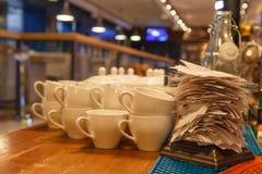 Weiße keramische Becher für Tee und Kontrollen von abgeschlossenen Aufträgen in t lizenzfreies stockfoto