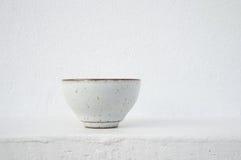 Weiße keramische Teeschale mit Zementwandhintergrund Stockfoto