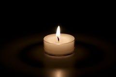Weiße Kerze auf einem schwarzen Hintergrund Lizenzfreie Stockfotografie