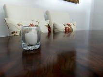 Weiße Kerze auf Holztisch mit weißen Stühlen lizenzfreie stockbilder
