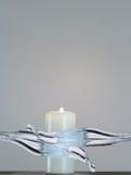 Weiße Kerze mit der Flamme, die mit Wasser gespritzt wird Stockbilder