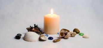 Weiße Kerze, Muscheln und farbige Kiesel Lizenzfreie Stockfotografie