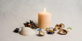 Weiße Kerze, Muscheln und farbige Kiesel Stockbilder