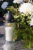 Weiße Kerze und künstliche Blumen auf einem Grab lizenzfreies stockbild