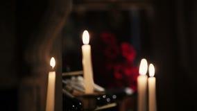 Weiße Kerzen Brennen Feuer Blumenstrauß der roten Rosen auf Hintergrund flamme stock footage