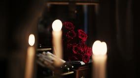 Weiße Kerzen Brennen Feuer Blumenstrauß von roten Rosen auf Hintergrund flamme stock video