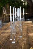 Weiße Kerzen in den Flaschen Wein stehen auf weißer Tabelle Lizenzfreie Stockfotos